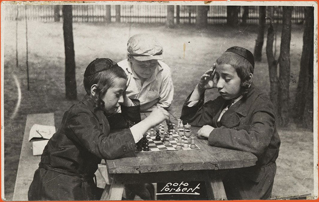 Three boys playing a game of chess