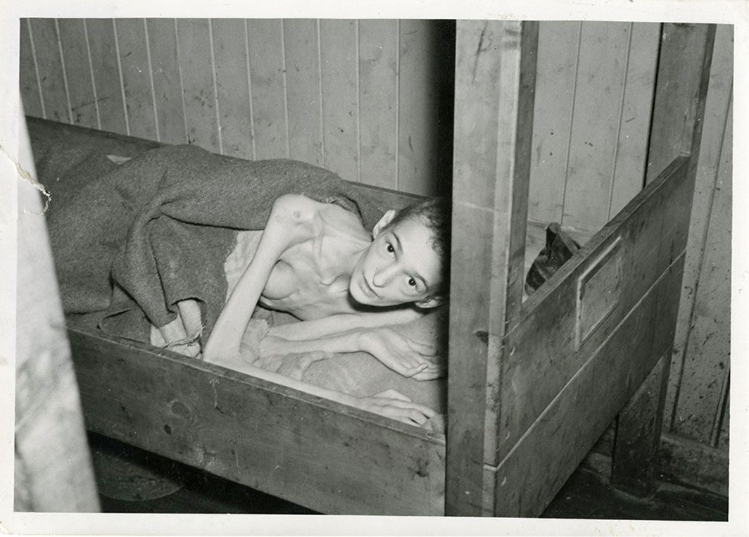 Photograph of a liberated young man in a bunk