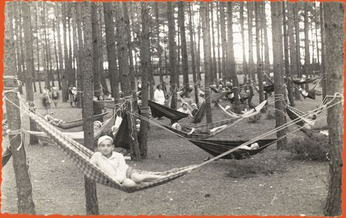 Children resting in hammocks in the woods