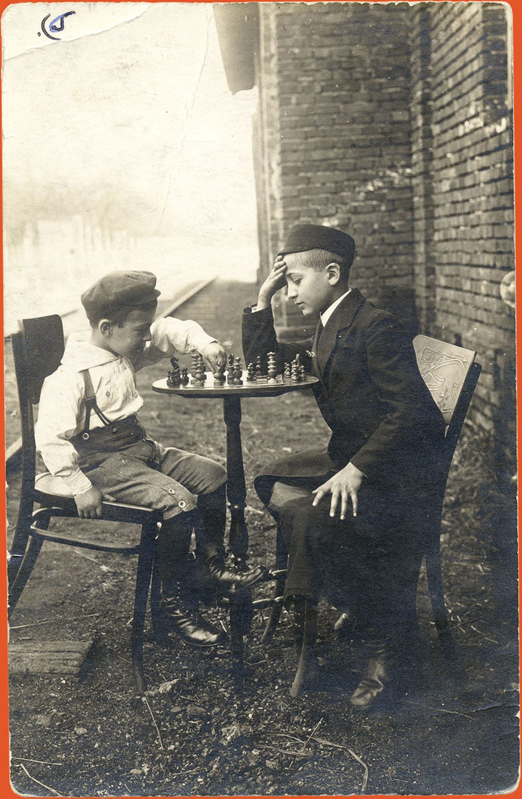 The boys sitting at a table and playing chess