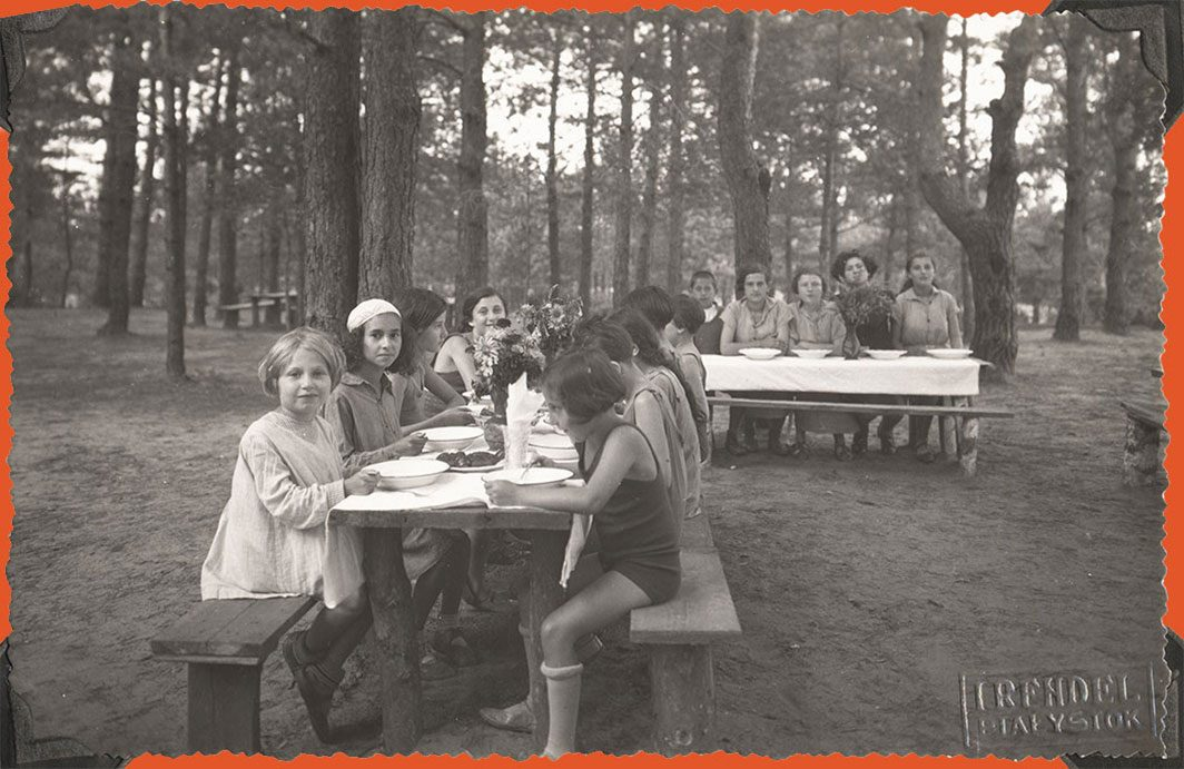 Children sitting down for a meal outside