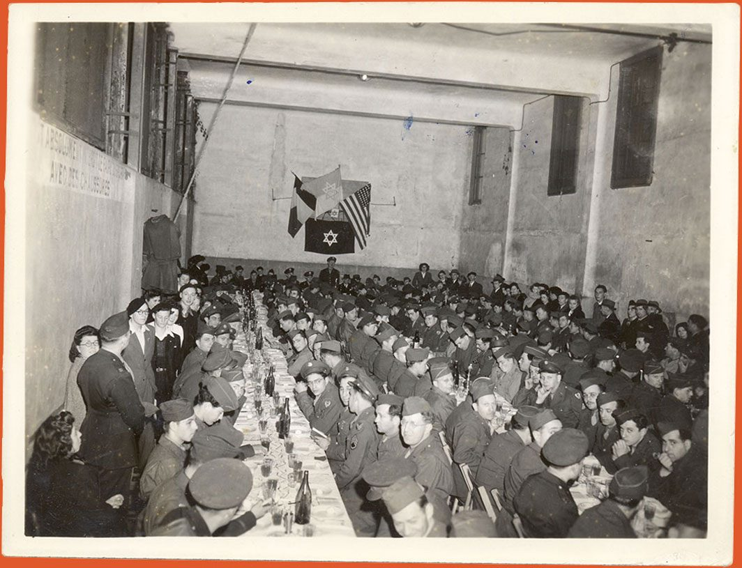 Room full of soldiers seated at a Passover Seder