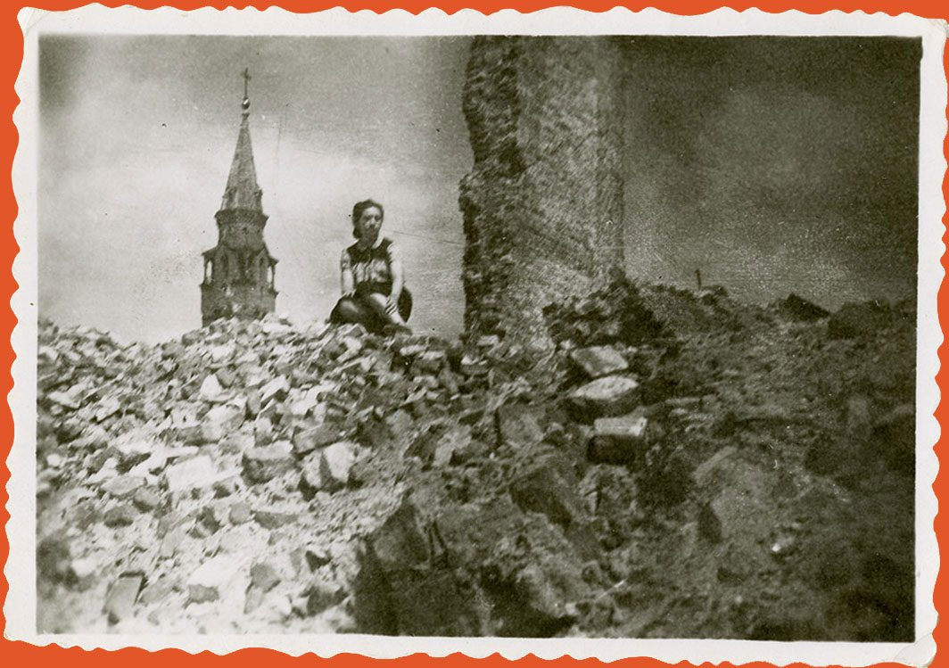 A woman sits in the ruins of the Warsaw Ghetto