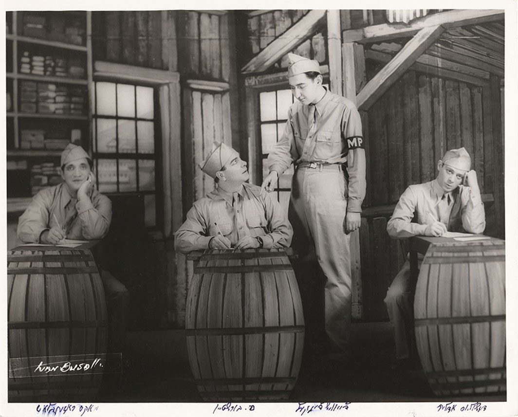 Four actors in army uniform performing a Yiddish play